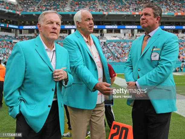 Former Miami Dolphin quarterbacks from left Bob Griese Don Strock and Dan Marino watch the game from the sidelines against the Los Angeles Chargers...