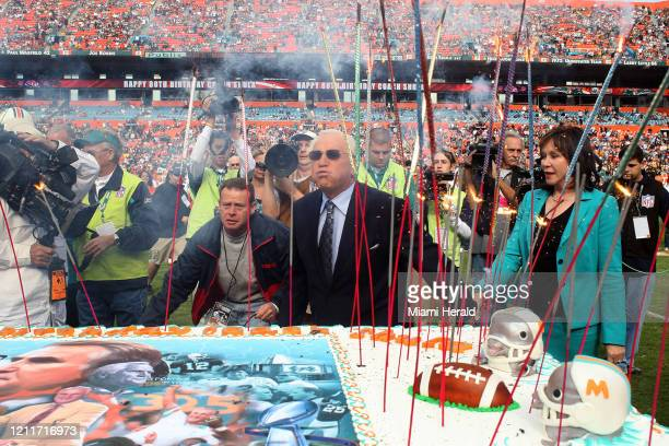 Former Miami Dolphins head coach Don Shula Blowing Out Candles center and his wife Mary Anne stand near a birthday cake on the field during a...