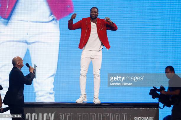 Former Miami Heat player Dwyane Wade jumps on the scorers table during the Miami Heat Dwyane Wade L3GACY Celebration at American Airlines Arena on...