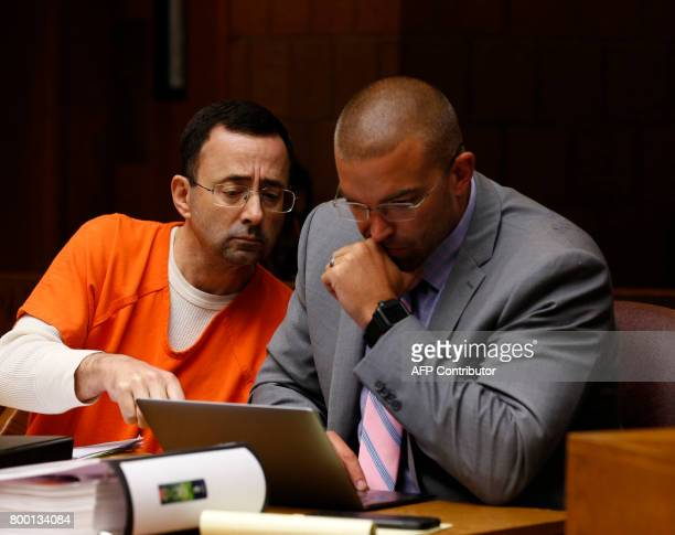 Former Michigan State University and USA Gymnastics doctor Larry Nassar with defense attorney Matt Newberg in the 55th District Court where Judge...