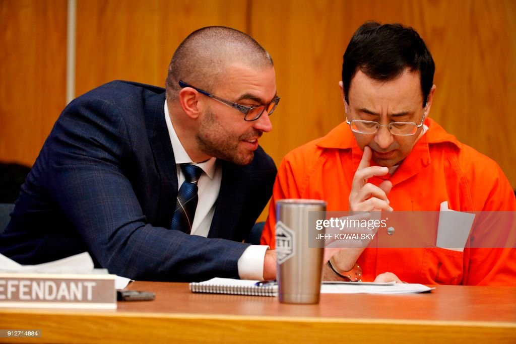 Former Michigan State University and USA Gymnastics doctor Larry Nassar talks to his defense attorney Matt Newberg (L) during the sentencing phase in Eaton, County Circuit Court on January 31, 2018 in Charlotte, Michigan. The number of identified sexual abuse victims of former USA Gymnastics doctor Larry Nassar has grown to 265, a Michigan judge announced Wednesday as a final sentencing hearing commenced. Prosecutors said at least 65 victims were to confront Nassar in court, in the last of three sentencing hearings for the disgraced doctor who molested young girls and women for two decades in the guise of medical treatment. KOWALSKY