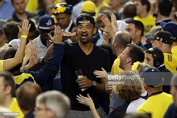 Former Michigan Wolverines player Juwan Howard greets Michigan fans in the stands against the Louisville Cardinals during the 2013 NCAA Men's Final...