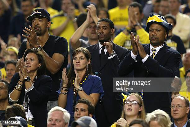 Former Michigan Wolverines players Juwan Howard Jimmy King and Jalen Rose cheer for Michigan in the first half against the Louisville Cardinals...