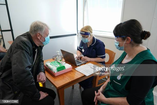 Former Middlesbrough Football Club player, Gary Pallister, gives his details as he receives his AstraZeneca/Oxford University Covid-19 vaccine at the...