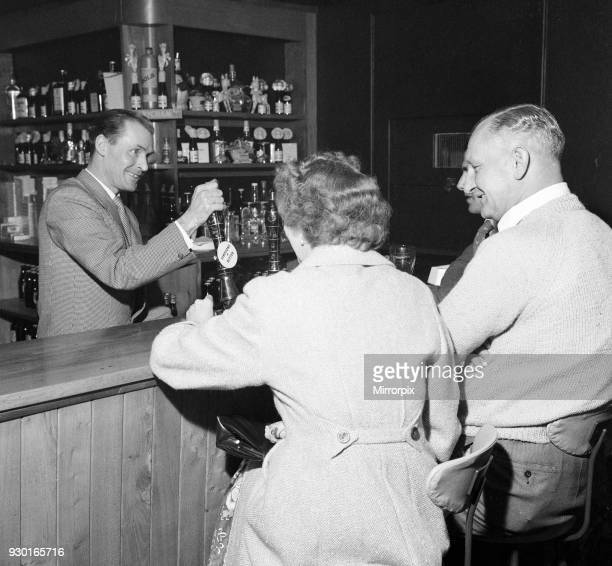 Former Middlesbrough footballer Wilf Mannion serving customers at the bar in his pub, 19th April 1959.