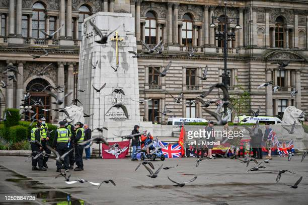 Former military personnel stand in front of the cenotaph in George Square on June 27, 2020 in Glasgow, Scotland. Activists have gathered in George...
