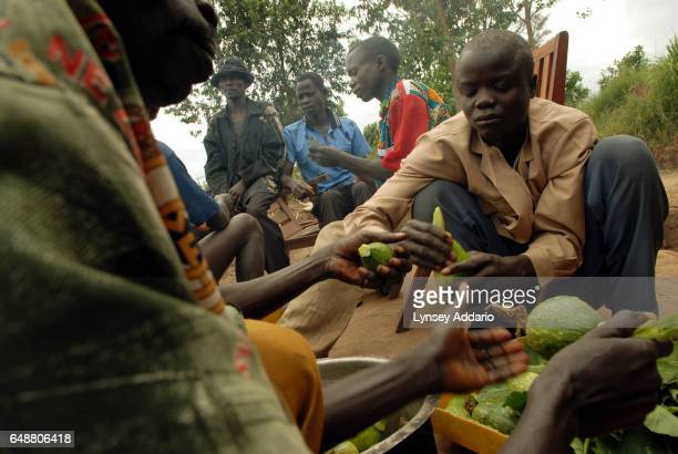 Former militiamen from the village of Bukuringi play cards and hang around after giving themselves up to UN peacekeepers and being disarmed as a part...