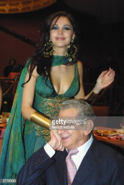 Former Miss Lebanon Joelle Behlok holds hands with Egypt's veteran film director Youssef Chahine during the 2003 Murrex D'Or film awards ceremony at...