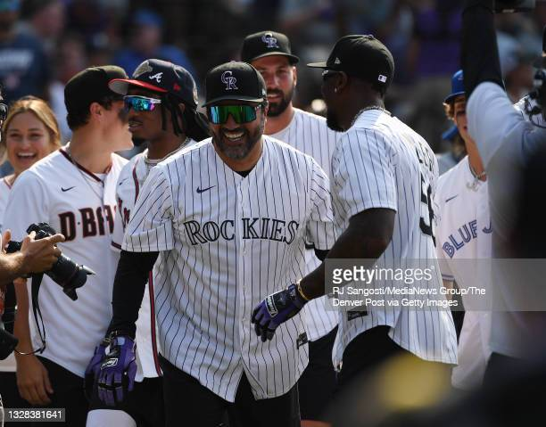 Former MLB infielder Vinny Castilla, center, celebrates with teammates after hitting a home run during the MLB All-Star celebrity softball game at...