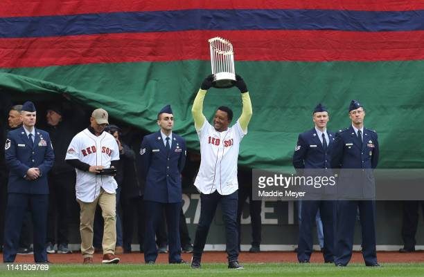 Former MLB player Pedro Martinez walks on the field with the 2018 World Series Championship trophy before the home opener at Fenway Park on April 09...