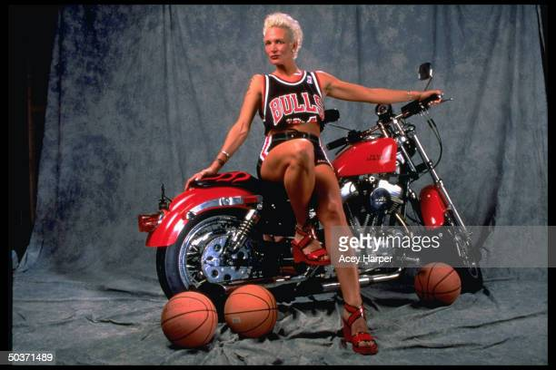 Former model Anicka Bakes Rodman whose exhusband is pro basketball player Dennis Rodman wearing Chicago Bulls uniform while posing on motorcycle