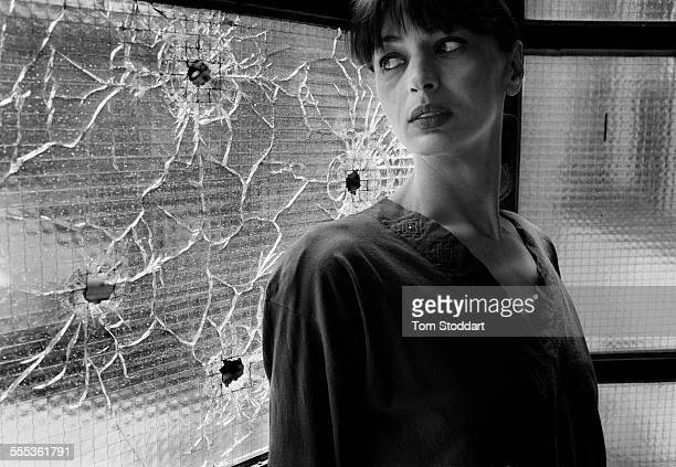 Former model Mirjana Deak photographed at home near windows shattered by sniper bullets during the siege of the city that would last for 47 months...
