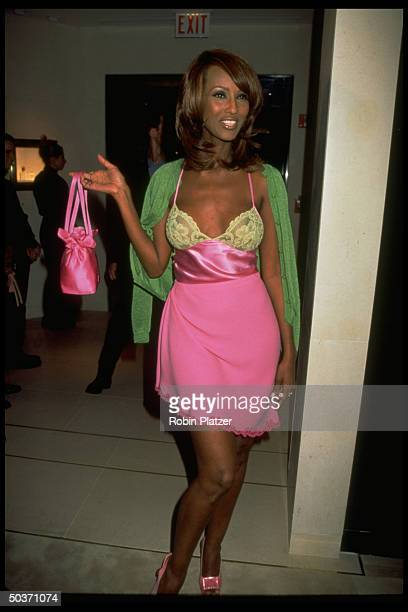 Former model/businesswoman Iman wearing pink yellow slip dress by Versace while holding matching pink satin handbag at opening party for Chanel...