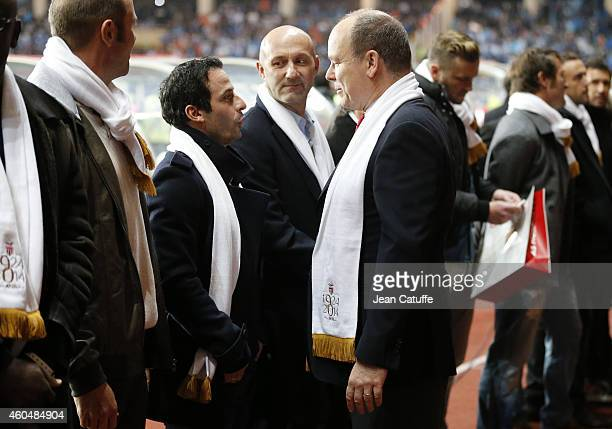 Former Monaco's player Ludovic Giuly salutes Prince Albert II of Monaco while Fabien Barthez looks on during the 90th club's anniversary tribute...
