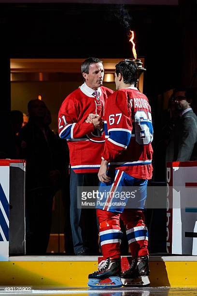 Former Montreal Canadiens captain and coach Guy Carbonneau hands over the flame to captain Max Pacioretty during the pre game ceremony prior to the...
