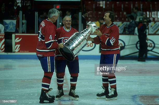 Former Montreal Canadiens Jean Beliveau Henri Richard and Guy Lafleur hold up the Stanley Cup Trophy before the 1993 44th NHL AllStar Game with the...