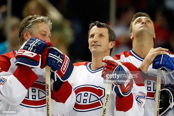 Former Montreal Canadiens Lyle Odelein Guy Carbonneau and Stephane Richer watch the Centennial Celebration ceremonies prior to the NHL game between...