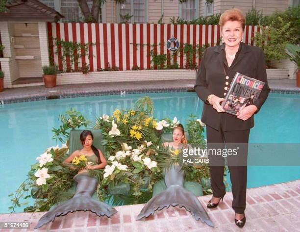 Former movie star Esther Williams poses for photographers poolside at the Chateau Marmont Hotel 11 May with two woman dressed as mermaids Williams...