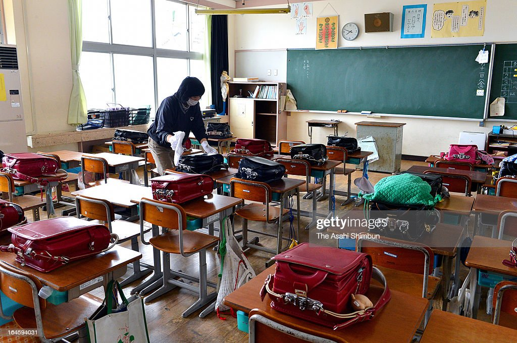 Former Namie Elementary School teacher Masako Tsushima cleans former her classroom that remains untouched after the Fukushima Daiichi Nuclear Power Plant meltdown, on March 23, 2013 in Namie, Fukushima, Japan. Japanese government will reclassify the radiation contaminated town by the radioactive level from April 1.