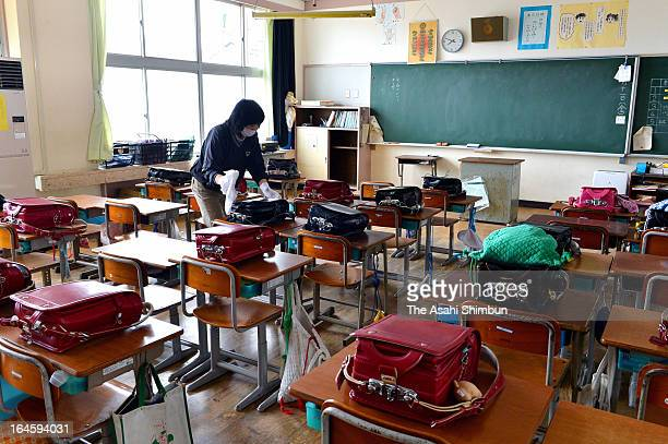 Former Namie Elementary School teacher Masako Tsushima cleans former her classroom that remains untouched after the Fukushima Daiichi Nuclear Power...
