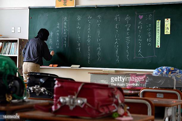 Former Namie Elementary School teacher Masako Tsushima leaves a message to her pupils after cleaning the classroom that remains untouched after the...