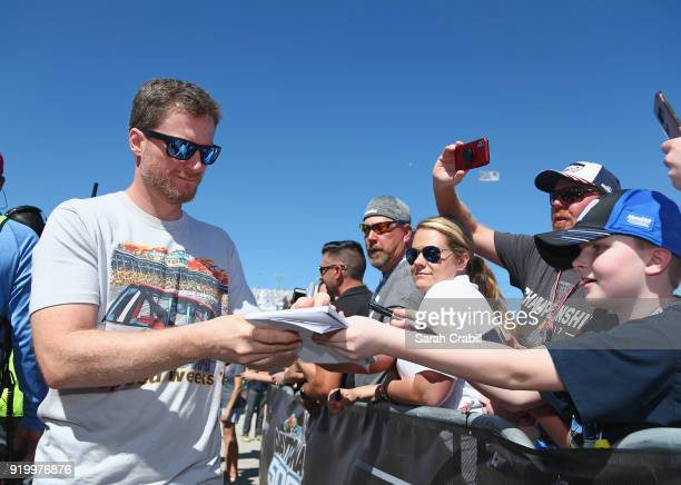 Former NASCAR driver Dale Earnhardt Jr signs autographs prior to the start of the Monster Energy NASCAR Cup Series 60th Annual Daytona 500 at Daytona...