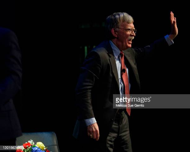 Former National Security Advisor John Bolton waves goodbye to the audience after discussing the current threats to national security during a forum...