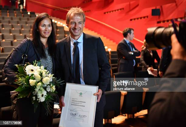 Former national soccer coach Juergen Klinsmann and his wife Debbie  posing after being awarded as Honourary Team Captain of the German National...
