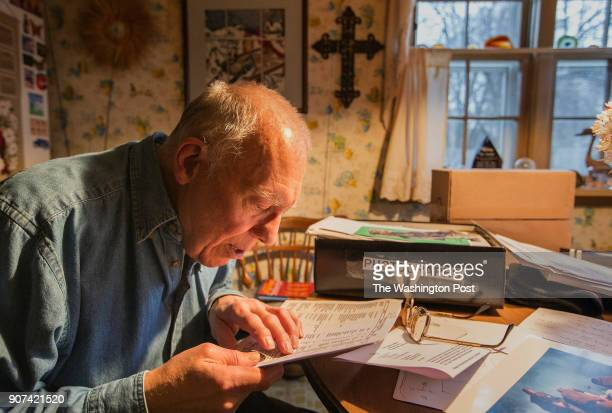 Former Naval Chaplain Ray Stubbe of Wauwatosa Wi looks over a list of names of some of the people he served with during the Siege of Khe Sanh in Viet...