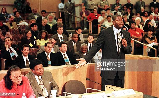 Former NBA basketball star Earvin Magic Johnson gestures towards boxing great Muhammad Ali and Ali's wife Lonnie during the Nevada State Athletic...