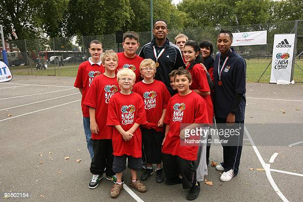 Former NBA player BJ Armstrong and Ros Mason of the Eurobasketball Women's team pose with children at a Special Olympic Clinic during the 2009 NBA...