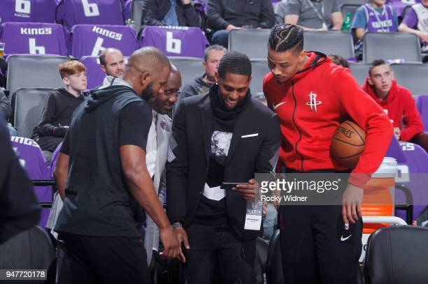 Former NBA player Bobby Jackson Chris Paul and Gerald Green of the Houston Rockets look at a phone prior to the game against the Sacramento Kings on...