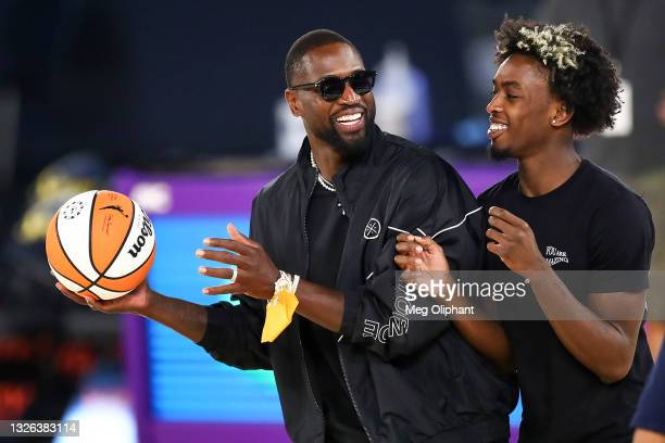 Former NBA player Dwyane Wade and his son Zaire Wade spend time on the court after the game between the Los Angeles Sparks and the Las Vegas Aces at...