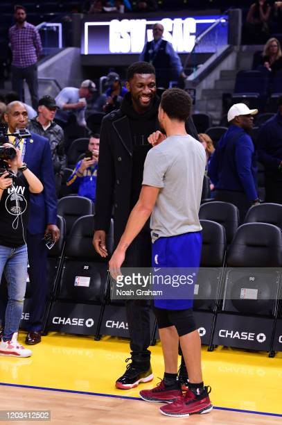 Former NBA player Festus Ezeli and Stephen Curry of the Golden State Warriors talk prior to a game against the Sacramento Kings on February 25, 2020...
