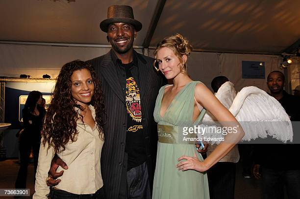 Former NBA player John Salley and wife pose with the Gran Centenario angel during Mercedes Benz Fashion Week held at Smashbox Studios on March 21...