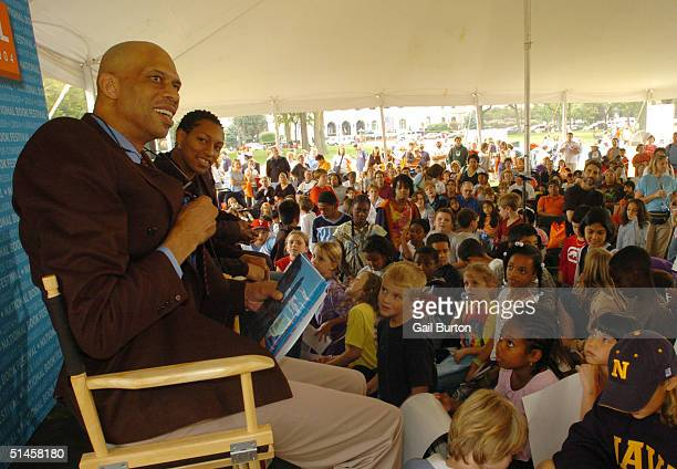 Former NBA player Kareem AbdulJabbar and WNBA player Muriel Paige read to children during the NBA Read to Achieve event during the National Book...