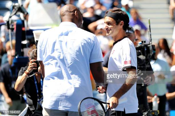 Former NBA player Kobe Bryant shakes hands with Roger Federer of Switzerland prior to his Men's Singles third round match against Daniel Evans of...