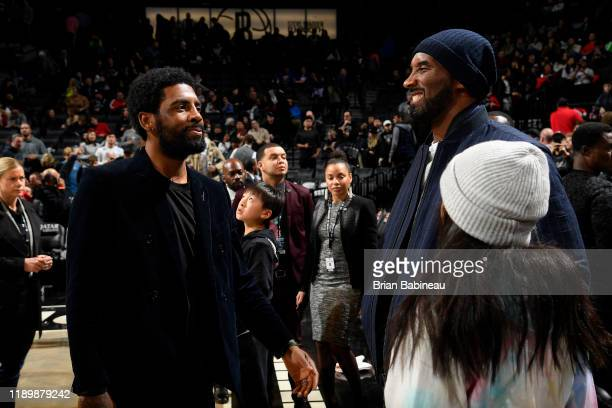 Former NBA Player, Kobe Bryant talks with Kyrie Irving of the Brooklyn Nets during the game against the Atlanta Hawks on December 21, 2019 at...