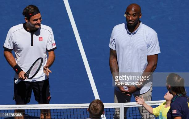 Former NBA player Kobe Bryant watches the coin toss as Roger Federer of Switzerland gets ready to play against Daniel Evans of Great Britain during...
