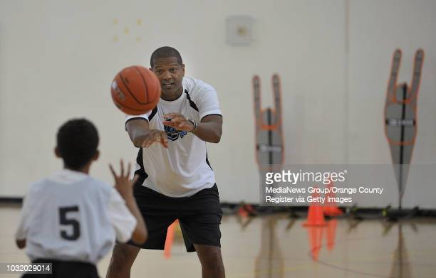 BEACH CALIF USA Former NBA player Marques Kevin Johnson left works with youngsters on the first day of the Pete Davis Legends Basketbal Camp at the...