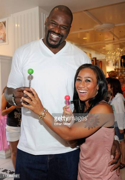 Former NBA player Shaquille O'Neal and television personality Nicole Hoopz Alexander joke around with couture lollipops at the Sugar Factory American...
