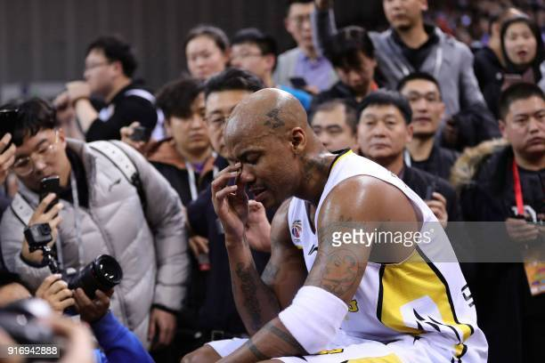 Former NBA player Stephon Marbury reacts as he is surrounded by media after his final game for the Chinese Basketball Association's Beijing Fly...