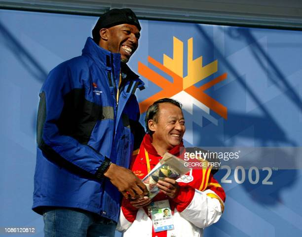 Former NBA player Thurl Bailey towers over Furong Li chief of mission for China's Olympic team as he receives gifts and is welcomed to the Olympic...