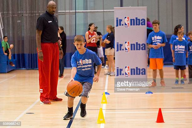 Former NBA player Vin Baker looks on while kids run drills during the Jr NBA skills competition regional finals held at Chelsea Piers in Stamford...