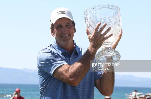 Former NBA player Vinny Del Negro celebrates with the trophy after winning the final round of the American Century Championship at Edgewood Tahoe...