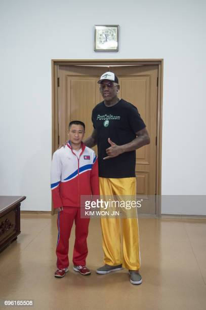 Former NBA star Dennis Rodman of the US poses with Olympic gymnast Ri Se Gwang of North Korea, at the Pyongyang Indoor Stadium on June 15, 2017...