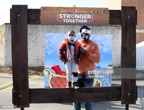 Former NBA star, Shaquille O'Neal takes photos with a guest for Pepsi Stronger Together and The Shaquille O'Neal Foundation's Holiday Market at Jones...