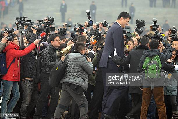 Former NBA star Yao Ming gets mobbed by media as he arrives for the opening session of the Chinese People's Political Consultative Conference at the...