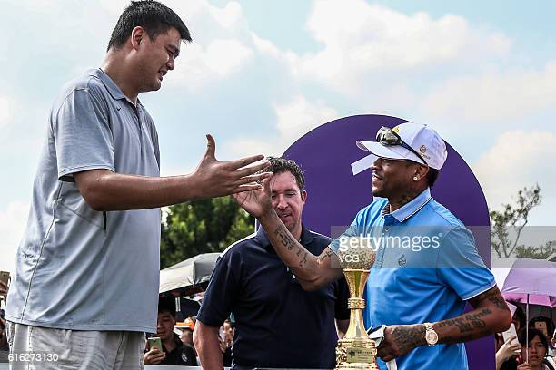 Former NBA star Yao Ming shakes hands with American retired basketball player Allen Iverson during the first day of 2016 Mission Hills World...