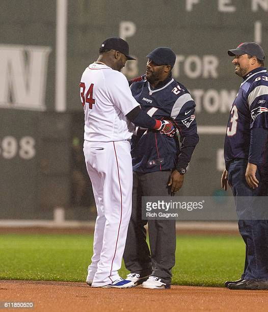 Former New England Patriot players Ty Law, Joe Andruzzi, Matt Chatham and Andre Tippett greet David Ortiz of the Boston Red Sox before a game against...